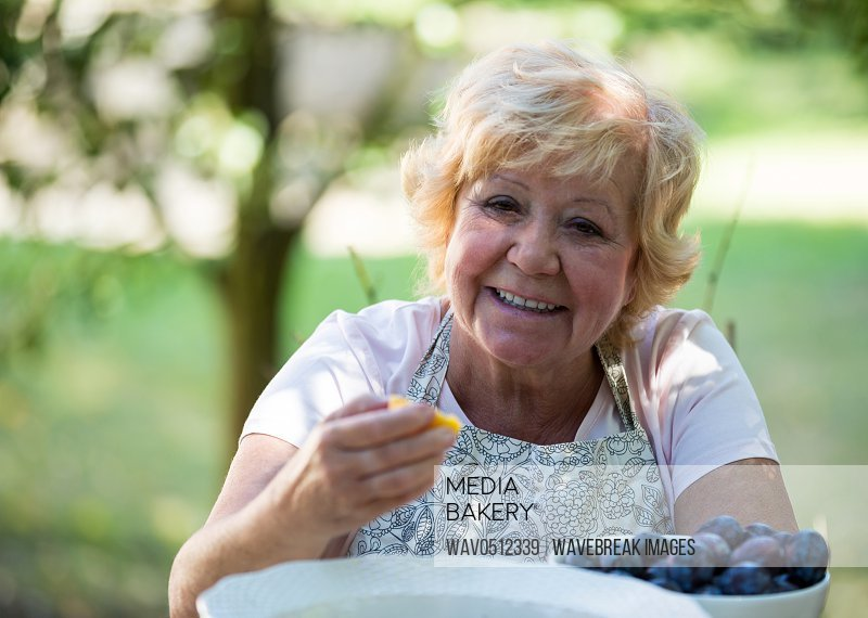 Portrait of senior woman having apricot in garden on a sunny day