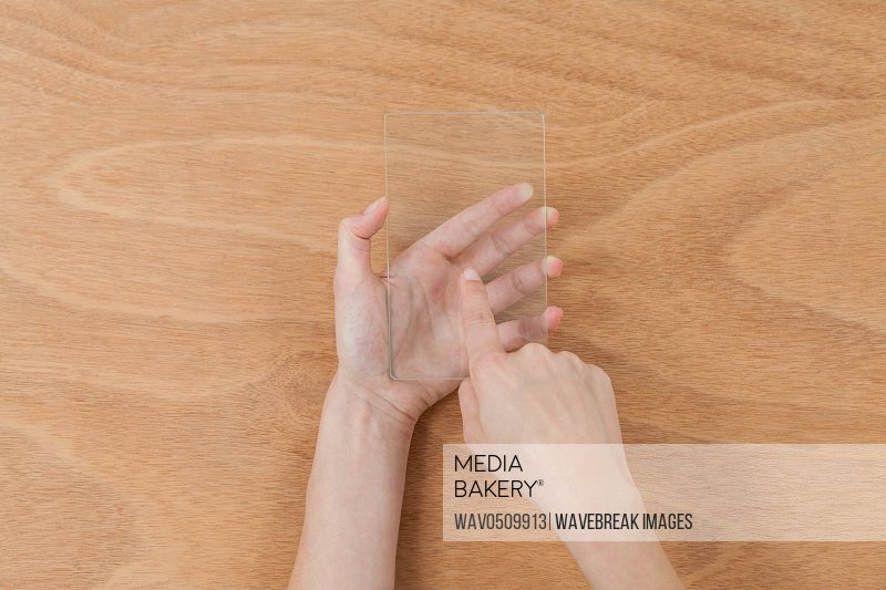 Close-up of hands pretending to use digital tablet against wooden background