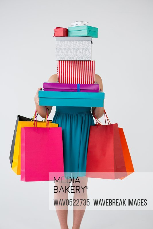 Woman carrying stack of gift boxes and shopping bags