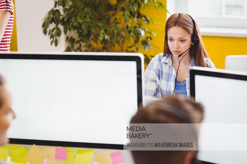 Confident young businesswoman working on computer at creative office