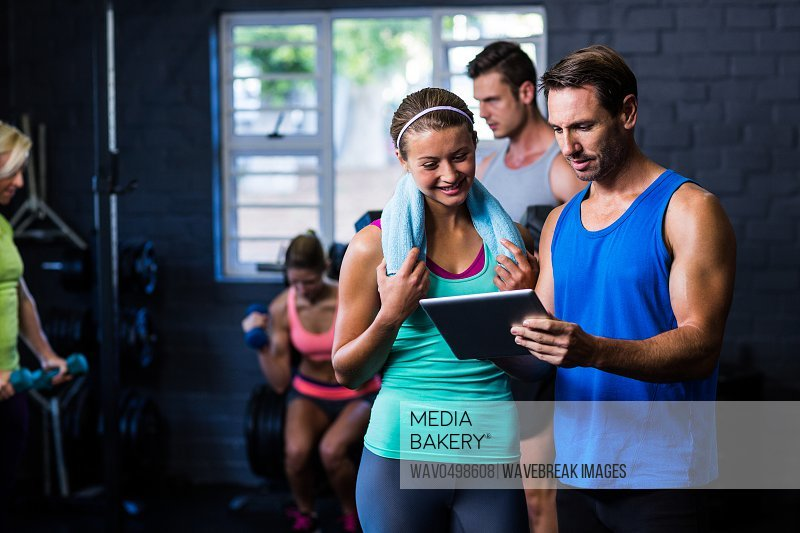 Young man and woman looking in tablet computer while standing in gym