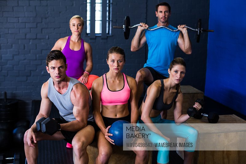 Determined athletes with exercise equipment in fitness studio