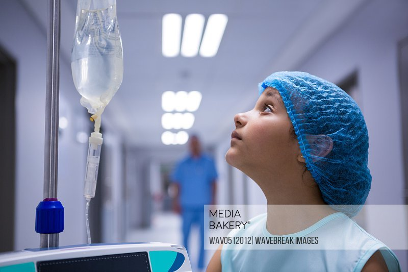Girl standing in corridor and looking at iv drip at hospital