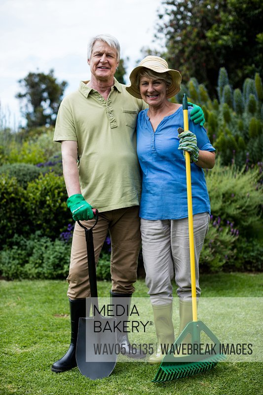 Portrait of senior couple standing with garden tools