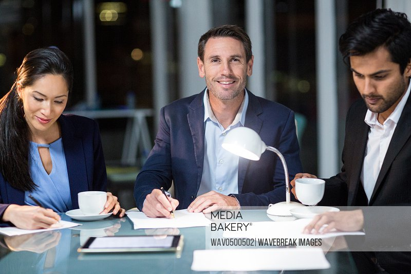 Businessman smiling at camera while colleagues writing on paper in the office