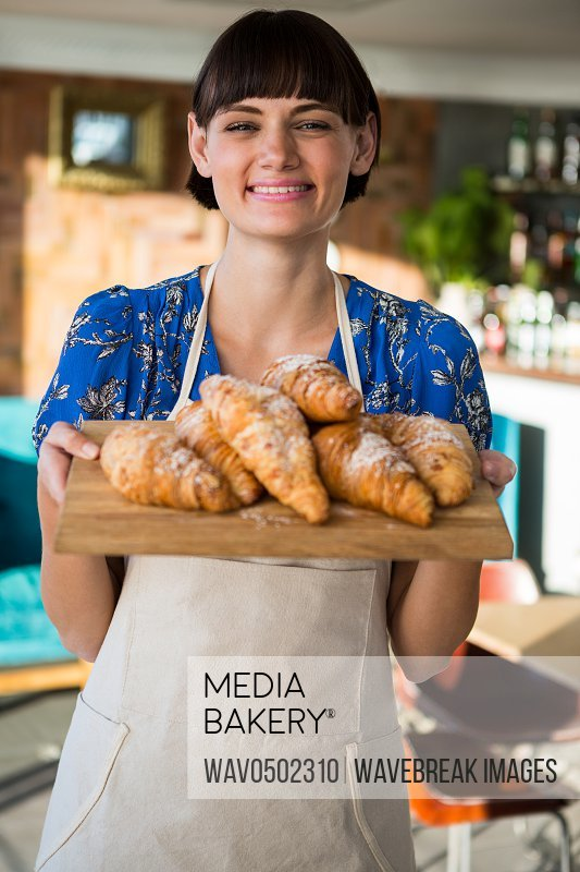 Smiling waitress holding a tray of croissants in the coffee shop