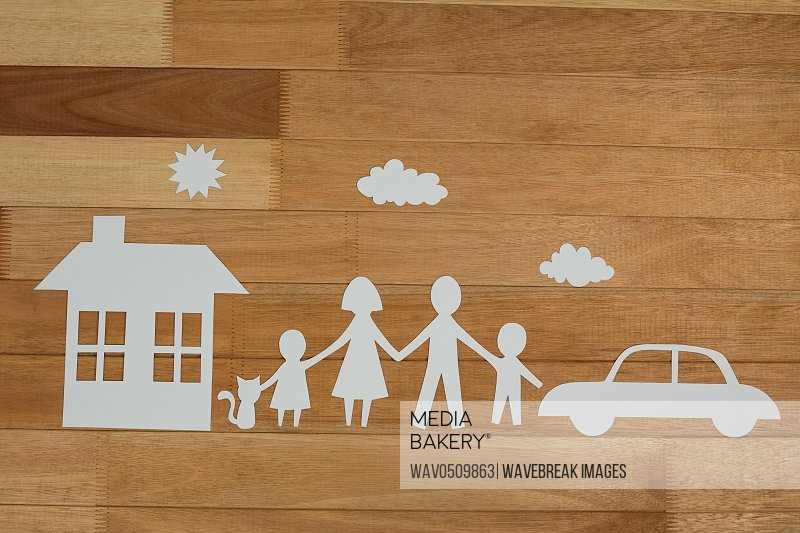 Paper cutout family with house and car on wooden plank