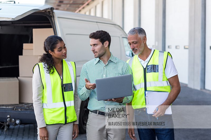 Manager and warehouse workers discussing with laptop near van