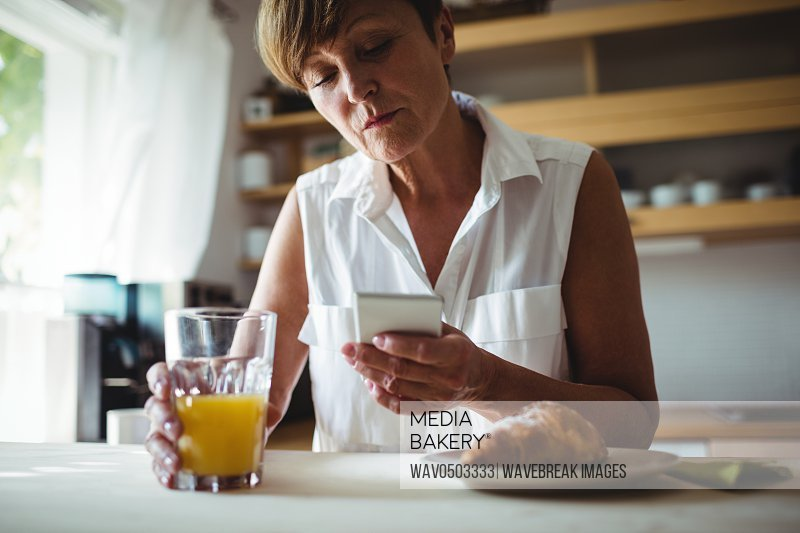 Senior woman using mobile phone while having breakfast in kitchen