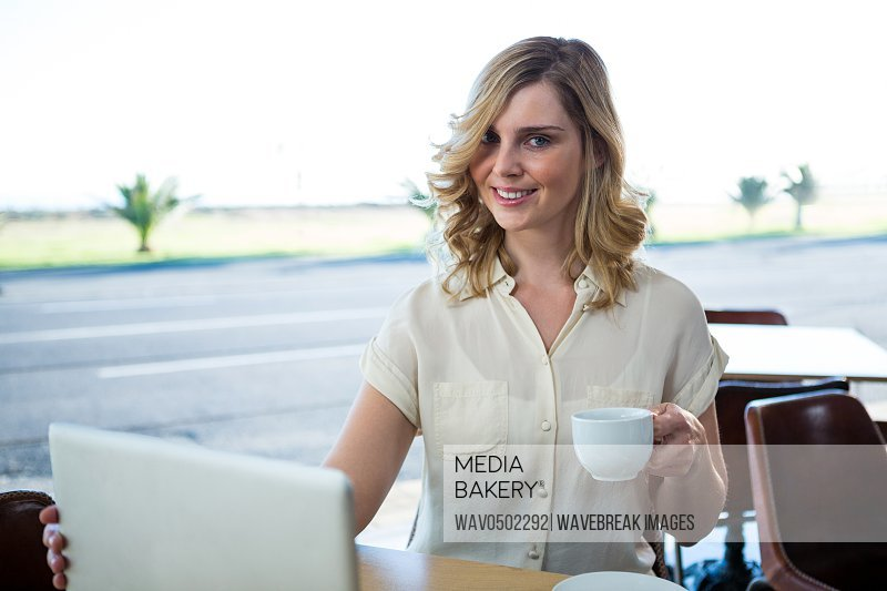 Portrait of smiling woman holding a laptop and coffee cup in coffee shop