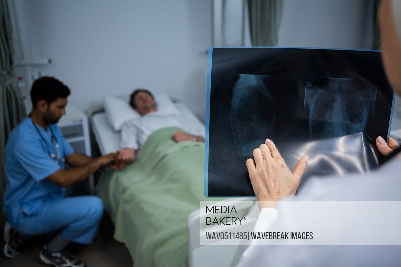 Doctor analyzing x-ray in ward while surgeon consulting patient in background