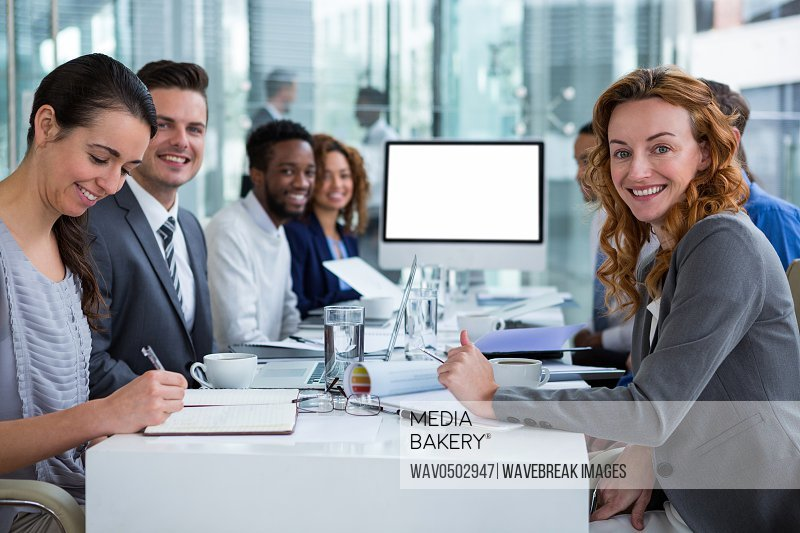 Portrait of happy businesspeople during video conference in office