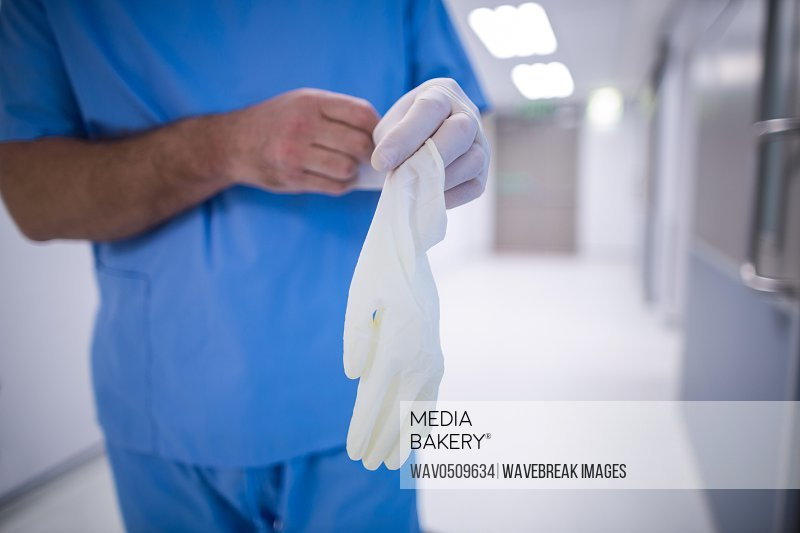 Mid section of surgeon wearing surgical glove at hospital