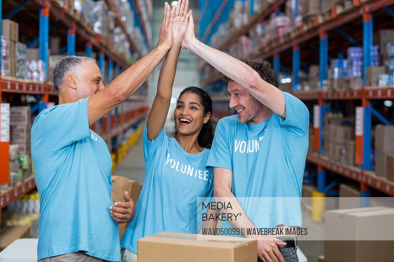 Three excited volunteers giving high five in the warehouse