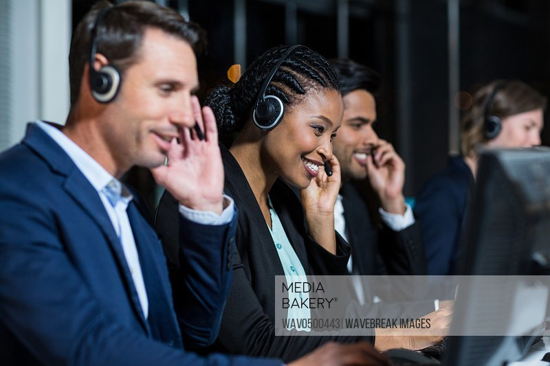 Group of business colleagues with headsets using computer at office desk