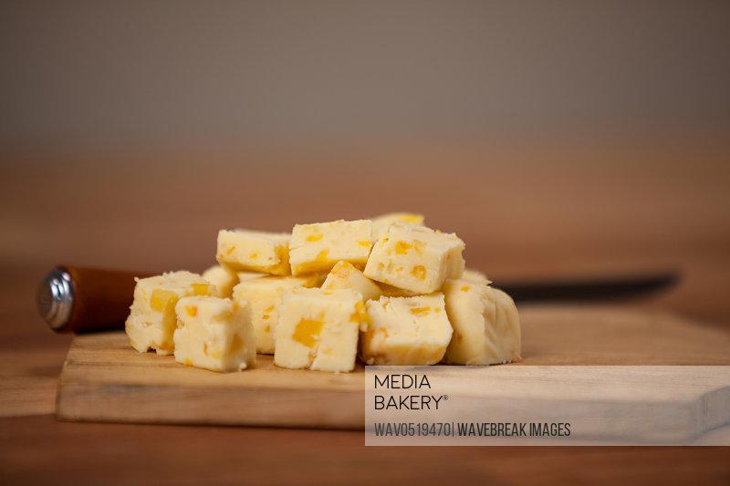 Cheese cubes on wooden chopping board