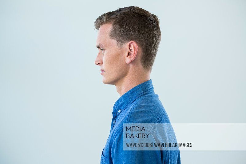 Side view of man in blue shirt against white background