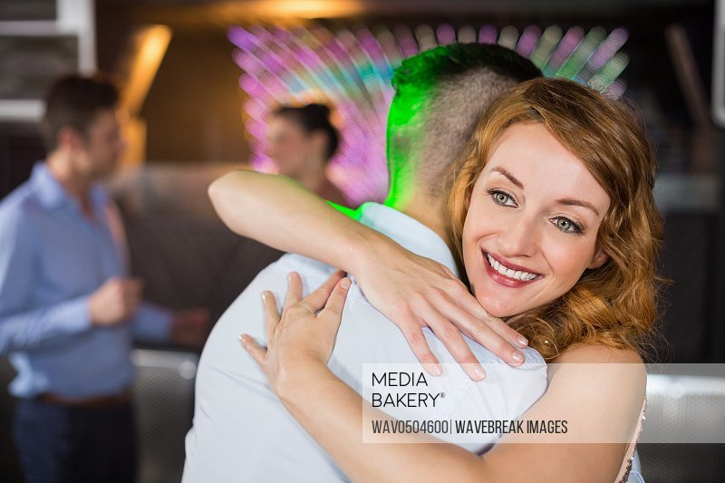 Smiling couple embracing each other in bar
