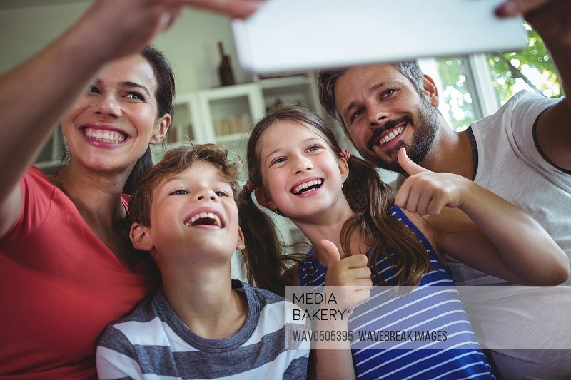 Happy family at taking a selfie at home with digital tablet