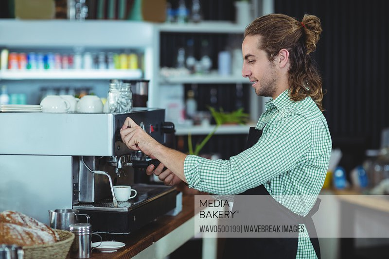 Waiter making cup of coffee in cafe