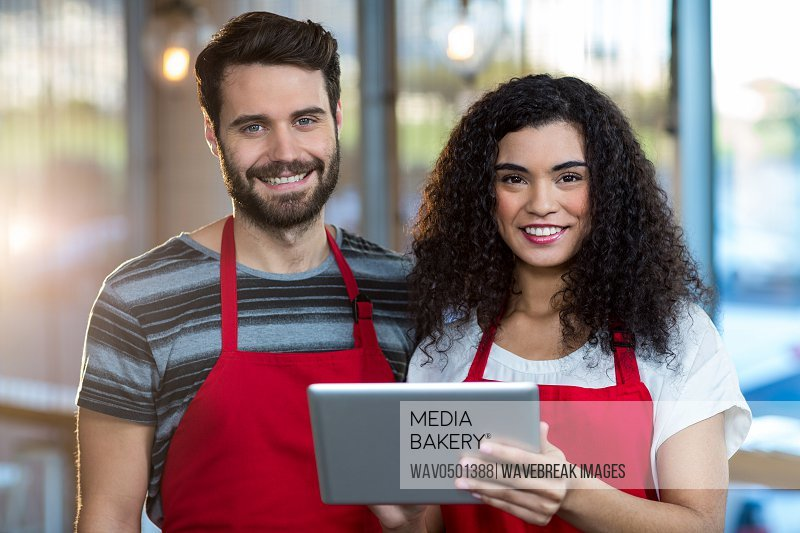 Portrait of smiling waiter and waitress using digital tablet at counter in cafe