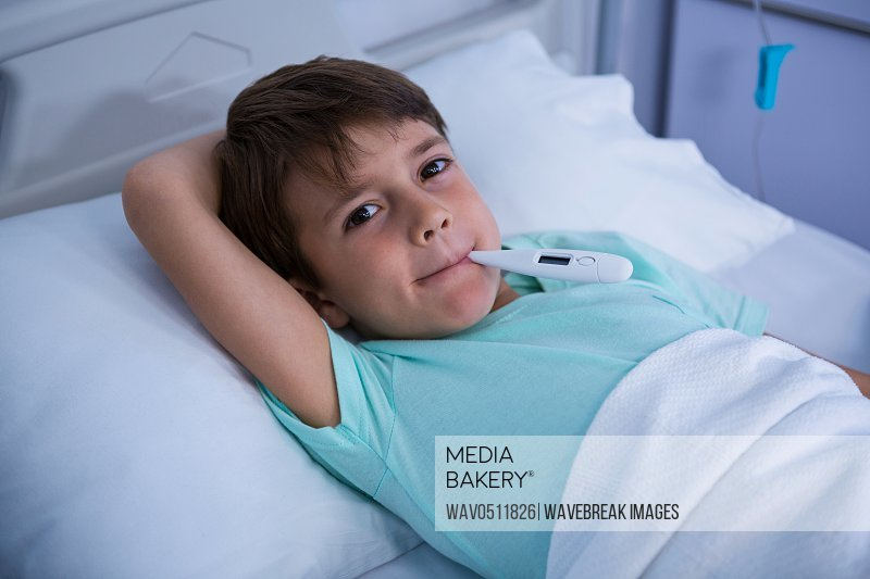 Portrait of patient lying on bed with thermometer in hospital