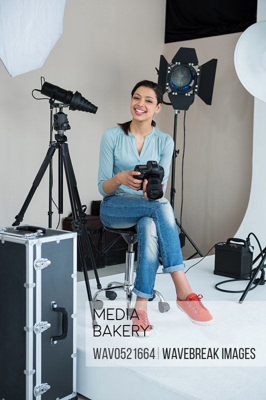 Happy female photographer in studio