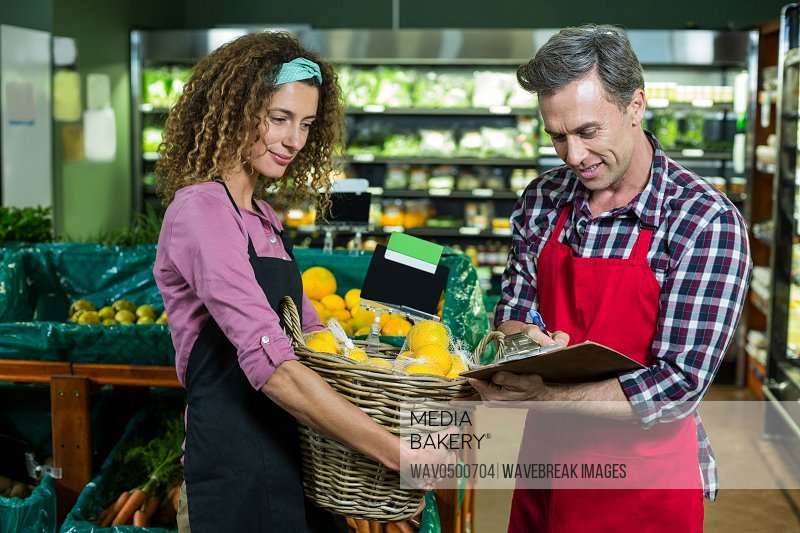 Female staff holding basket of fruit and male staff writing on clipboard in supermarket