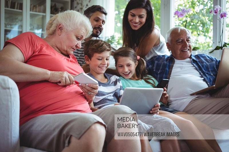 Happy multi-generation family sitting on sofa and using laptop mobile phone and digital tablet