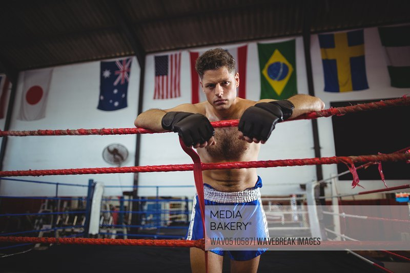 Portrait of tired boxer leaning on boxing ring