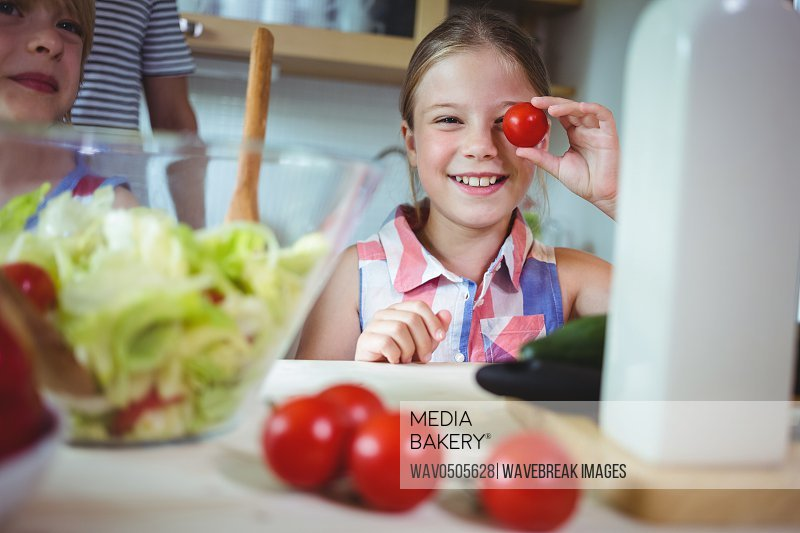 Playful girl holding cherry tomato on her eye in the kitchen