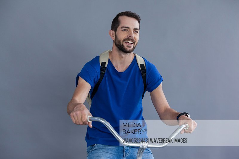 Man in blue t-shirt and back posing sitting on a bicycle