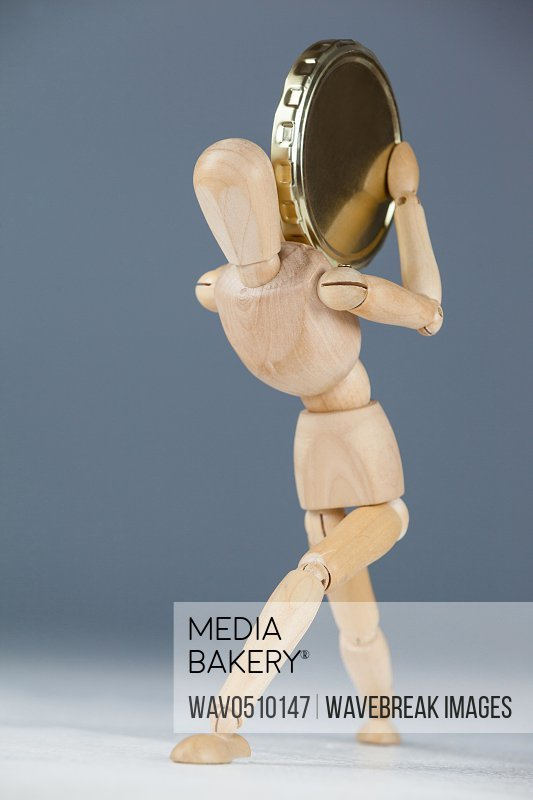 Wooden figurine holding a gold coin against white background