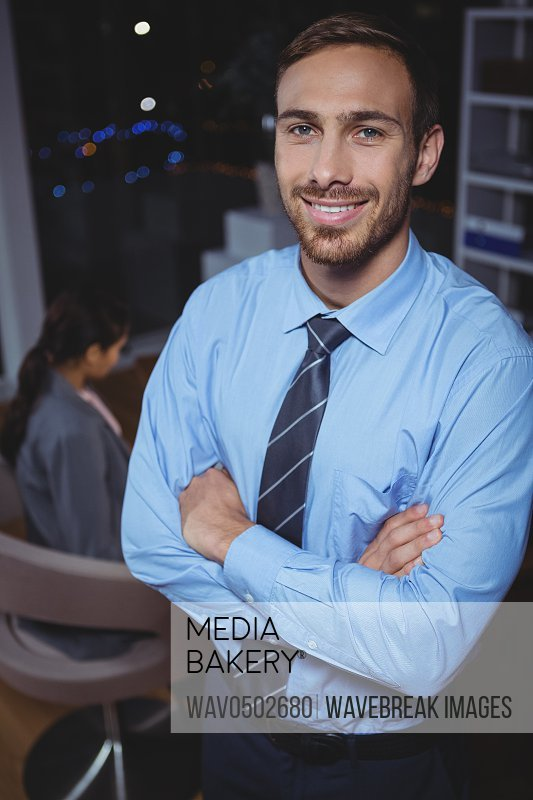Business executive standing with arms crossed in office at night
