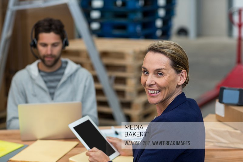 Portrait of warehouse manager using digital tablet in warehouse
