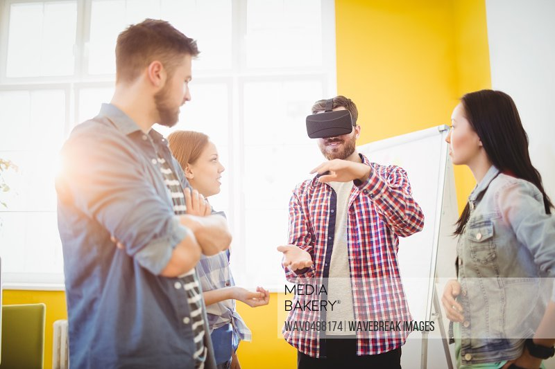 Colleagues looking at businessman wearing virtual reality headset in creative office