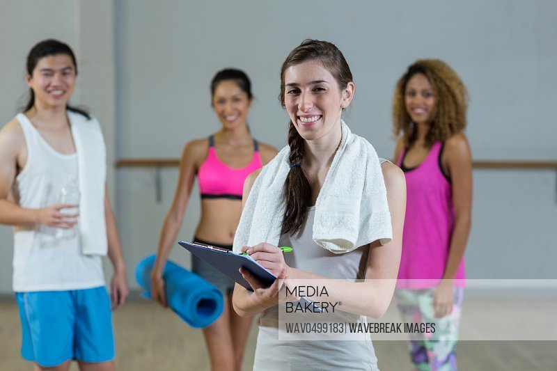 Portrait of female trainer holding clipboard with fitness class in background in fitness studio