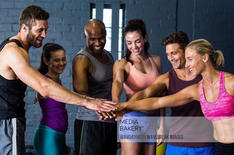 Happy male and female athletes stacking hands in gym