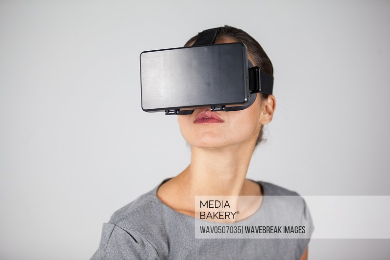 Woman using virtual reality headset against white background