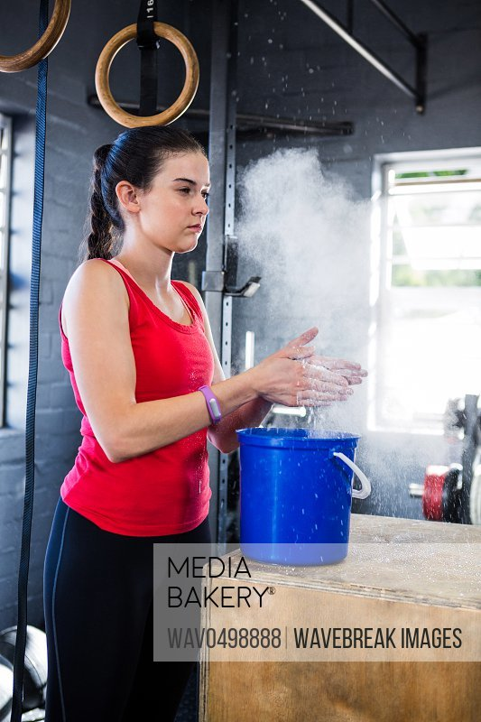 Female athlete rubbing sports chalk on hands while standing in gym