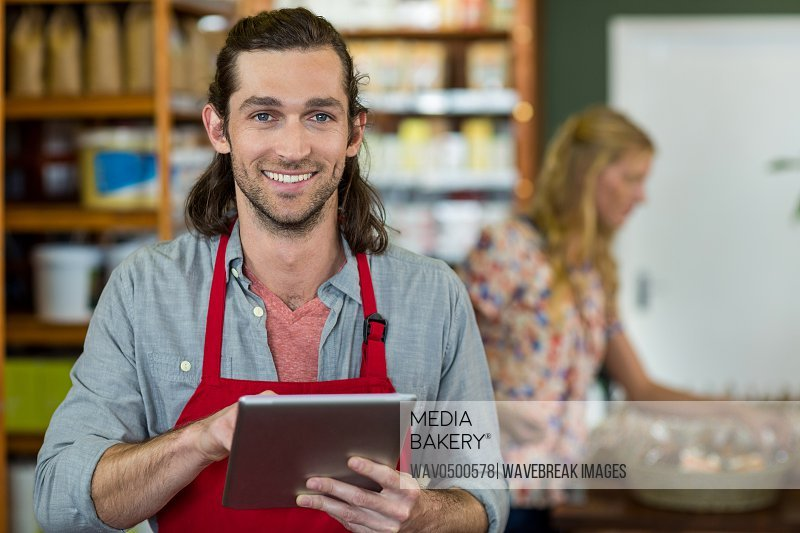 Portrait of smiling male staff using a digital tablet in supermarket