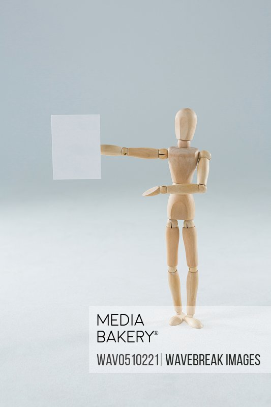 Wooden figurine holding blank placard against white background