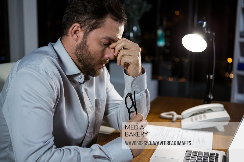 Frustrated businessman sitting in office at night