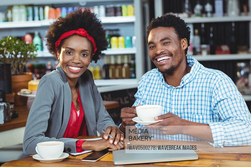 Portrait of man and woman having cup of coffee in cafe