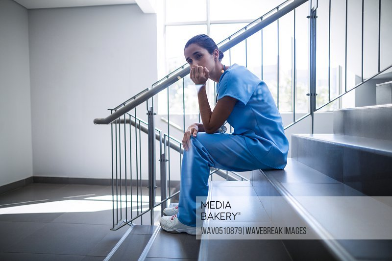 Upset female surgeon sitting on staircase of hospital