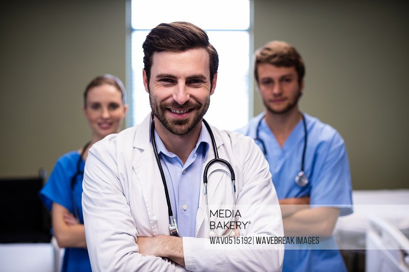 Portrait of male doctor and his colleague standing with arms crossed