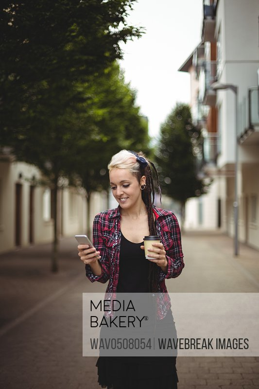 Happy woman using mobile phone while having coffee on street