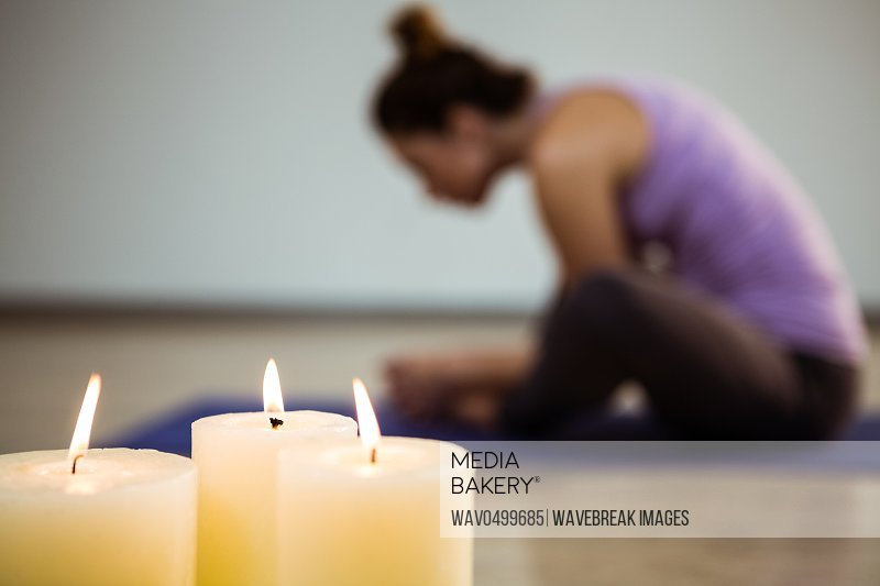 Close-up of three lit candles and blurred woman exercising in background