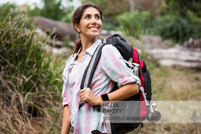 Smiling female hiker hiking in forest