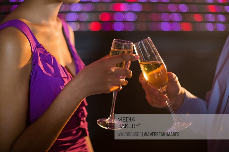 Mid section of couple toasting a glass of champagne in bar